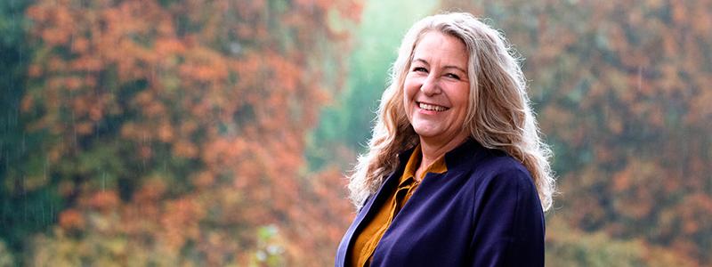 Smilende kvinde i efterårsskov